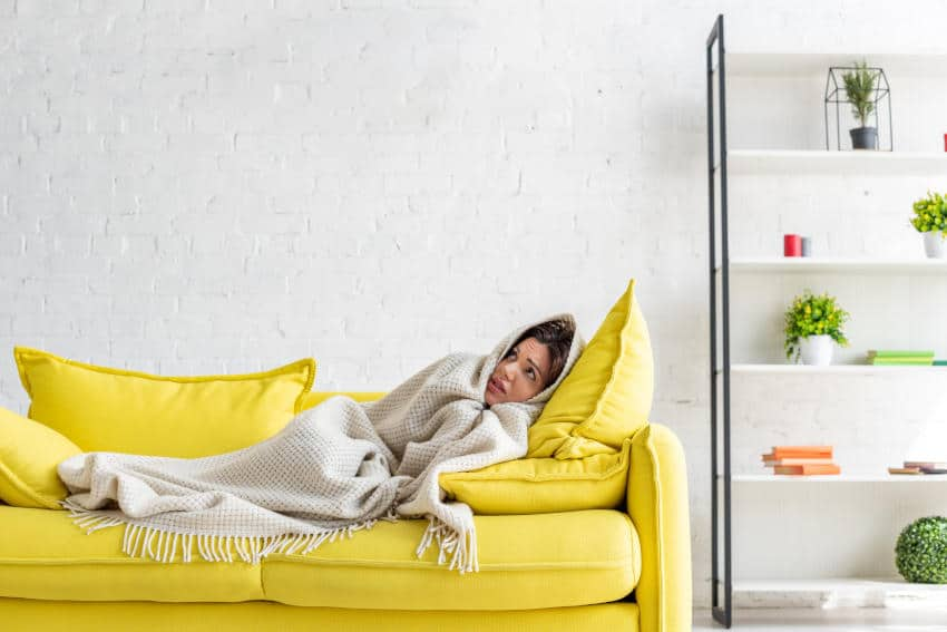 Frozen Women Trying to Warm up Under Blanket on Couch - No Unit