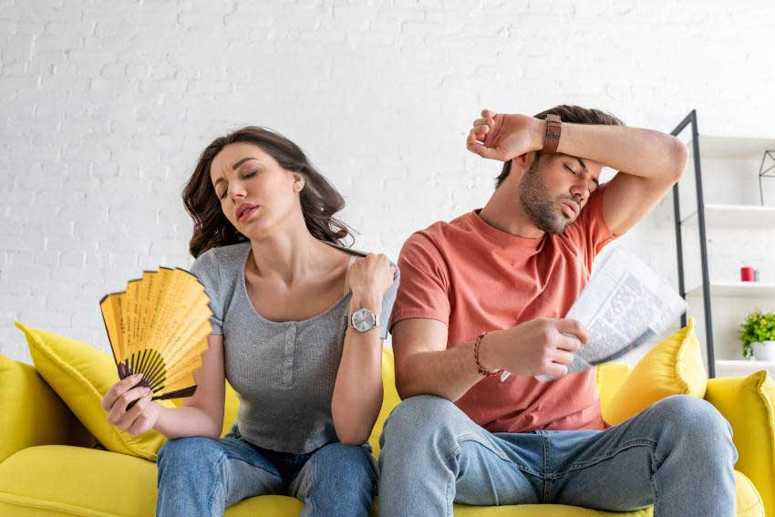 Uncomfortable-Hot-Couple-Sitting-on-Couch-Faning-the-Heat - No Unit